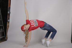 Nuori break-tanssijanainen poseeraamassa valokuvausstudiossa valkokankaan edessä, silta-asennossa, toinen käsi korkealla ilmassa.
