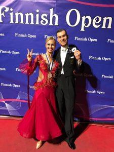 Luca Rossignoli ja Merje Styf hymyilevät iloisesti Finnish Openin mitalit kaulassa. Merje näyttää sormillaan voitonmerkkiä.