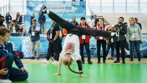 Lettipäinen tanssija käsinseisonnassa, jalat sivuspagaatissa