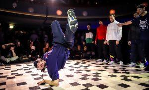 Break-tanssija lattialla käsivartensa varassa, jalat ilmassa