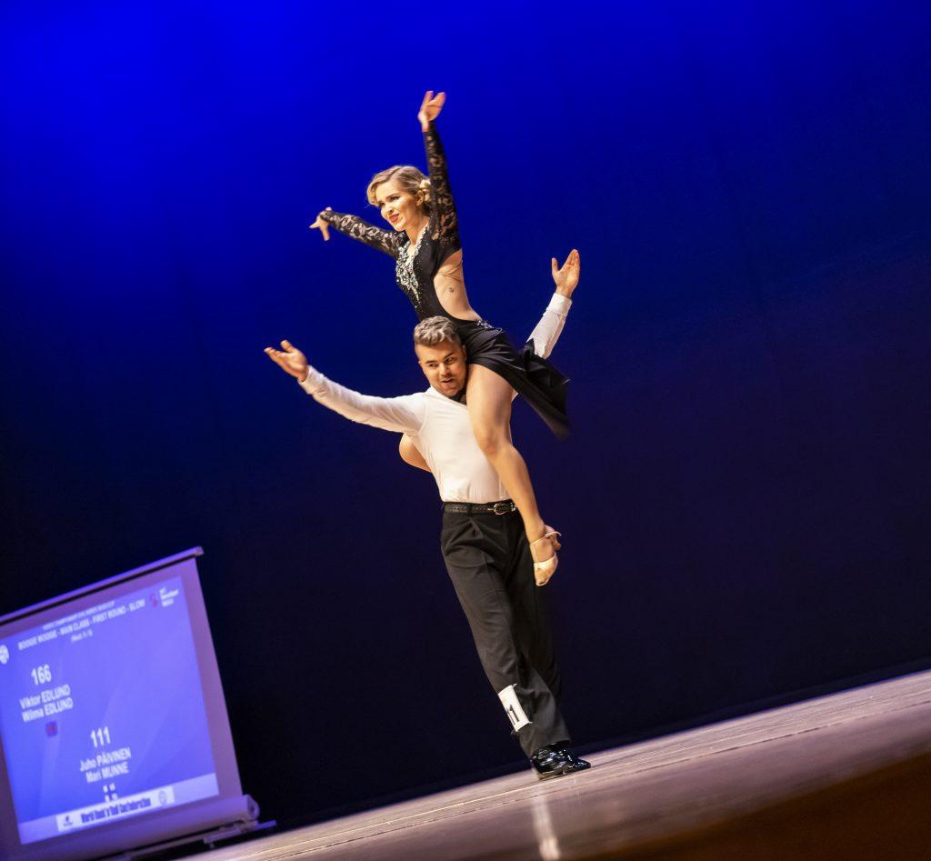 Juho Päivinen ja Mari Munne tanssimassa. Mari istuu Juhon olkapäällä, molemmilla kädet kohotettuna yläviistoon.