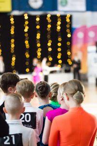 Lapsia ja nuoria selin katsomassa tanssiesitystä ja odottamassa vuoroaan
