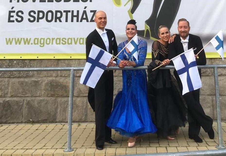 Parit Aleksi Volanen - Outi Pöntinen ja Pasi Rautio - Minttu Pajunen hymyilevät Suomen liput käsissään