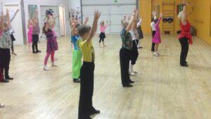 Tanssivia koululaisia kädet pään päällä